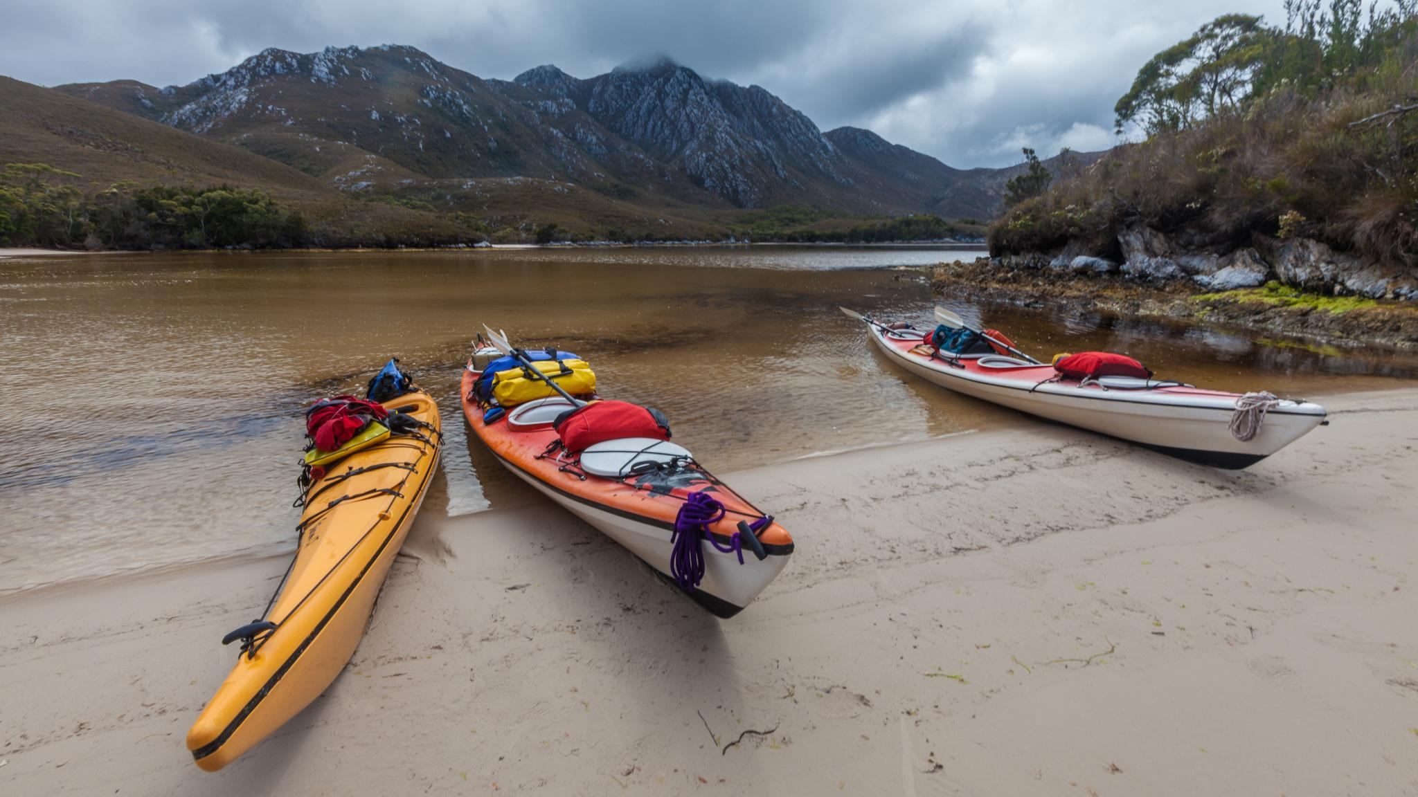 Kayakers on beach in Bramble Cove, Port Davey, Southwest Tasmania